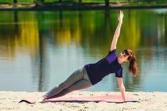 Brunetka w błękitnej sport koszula na sprawności fizycznej matowy robić ćwiczy na plaży Kobieta robi sprawności fizycznej ćwiczen Zdjęcie Royalty Free
