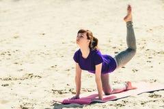 Brunetka w błękitnej sport koszula na sprawności fizycznej matowy robić ćwiczy na plaży Kobieta robi sprawności fizycznej ćwiczen Obraz Royalty Free