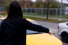 Brunetka w czerni sukni trwanie z powrotem zatrzymuje żółtego taxi fotografia stock