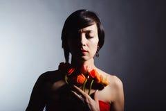 Brunetka w czerwonej sukni z kwiatami na białym tle Fotografia Royalty Free