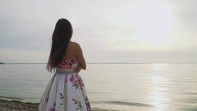 Brunetka w długiej sukni stoi bezczynnie rzekę zbiory