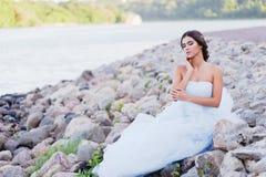 Brunetka w luksusowej sukni siedzi na bankach rzeczni wielcy kamienie i pluje twój twarz, Zdjęcia Royalty Free