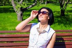 Brunetka w okularach przeciwsłonecznych śmia się w parku na słonecznym dniu Zdjęcia Royalty Free