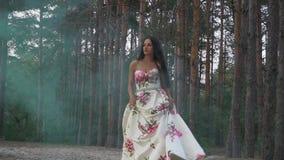 Brunetka w sukni chodzi w koloru dymu przeciw tłu las zbiory wideo