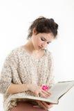 Brunetka w trykotowym puloweru obsiadaniu, czytaniu i książka Fotografia Stock