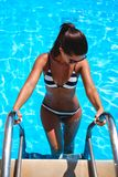 Brunetka wchodzić do pływackiego basenu i patrzeje w dół zdjęcia stock