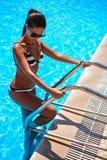 Brunetka wchodzić do pływackiego basenu schodkami obraz stock