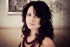 Brunetka z kędzierzawym włosy w czarnych bielizn spojrzeniach w lustrze Zdjęcie Royalty Free