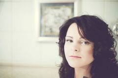 Brunetka z kędzierzawym włosy w czarnych bielizn spojrzeniach w lustrze Fotografia Stock