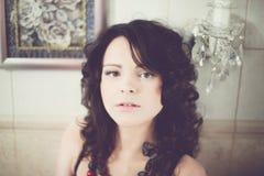 Brunetka z kędzierzawym włosy w czarnych bielizn spojrzeniach w lustrze Zdjęcia Stock