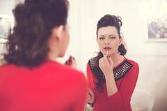 Brunetka z kędzierzawym włosy w czerwonej sukni barwi jej wargi w lustrze Obrazy Royalty Free