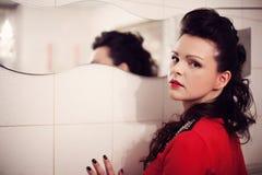 Brunetka z kędzierzawym włosy w czerwonej sukni blisko lustra Obrazy Royalty Free