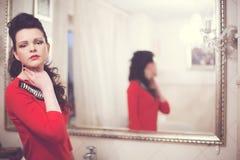 Brunetka z kędzierzawym włosy w sukni czerwonych spojrzeniach w lustrze Fotografia Stock
