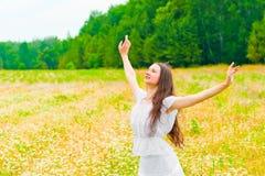 Brunetka z kwiatu polem z rękami szeroko rozpościerać strony Zdjęcie Stock