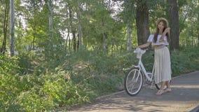 Brunetka z zadumanym spojrzeniem w słomianym kapeluszu, długiej spódnicie i bluzki białych stojakach z miasto bicyklem w parku, zbiory wideo