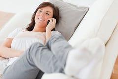 brunetki żeńska lying on the beach telefonu kanapa Zdjęcie Stock