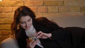 Brunetki caucasian dziewczyna z falistego włosy lying on the beach na kanapa zegarkach w smartphone i zwrotami kamera w cosy domo zbiory wideo