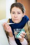 Brunetki choroba z febrą pod koc w domowym wnętrzu Zdjęcia Stock