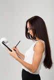 Brunetki damy writing papieru klamerki biznesowa deska Fotografia Royalty Free