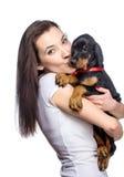 Brunetki dziewczyna gryźć jej doberman szczeniaka ucho Zdjęcia Royalty Free