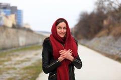 Brunetki dziewczyna jest ubranym czarną skórzaną kurtkę z czerwonym szalikiem zdjęcia stock