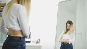 Brunetki dziewczyna w bielu wierzchołka talii taśmy miarą w przodu lustrze miarze zbiory wideo