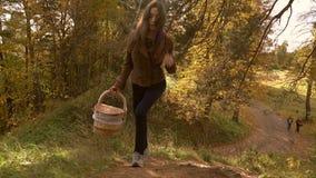 Brunetki dziewczyna w brown kurtce z koszykowy chodzący ciężkim w jesieni drewnach Wspinaczkowy ciężki 4K steadicam strzał zbiory