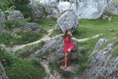 Brunetki dziewczyna w czerwieni smokingowy jest usytuowanym jeden wapień Zdjęcie Stock