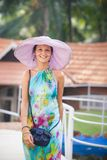 Brunetki dziewczyna w kwiat sukni i menchia kapeluszu Zdjęcie Stock