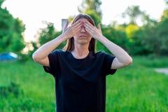Brunetki dziewczyna w lecie w parkowej naturze Gesty ręki zamykali ona oczy peekaboo Emocjonalni gesty Fotografia Royalty Free