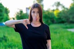 Brunetki dziewczyna w lecie w parku outdoors Pokazuje jego palcowego puszek Rozczarowywa negatyw Pokazuje języka Emocje a obraz stock