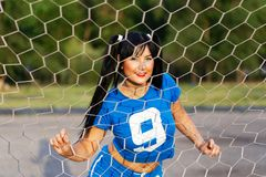 Brunetki dziewczyna w sporta munduru stojakach za futbolowym gat obraz stock