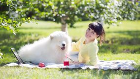 Brunetki dziewczyna z białym psem na naturze zdjęcie royalty free