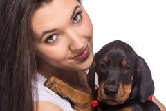 Brunetki dziewczyna z jej szczeniakiem odizolowywającym na białym tle Zdjęcie Stock