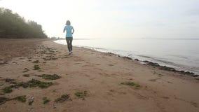 brunetki dziewczyna zaczyna biegać na plaży przy świtem zbiory