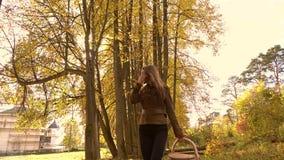 Brunetki dziewczyny odprowadzenie w jesień lesie trzyma kosz 4K steadicam klamerka zdjęcie wideo