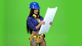 Brunetki dziewczyny ono uśmiecha się rozwija się papier z rysunkiem i czyta je na zielonym tle zdjęcie wideo