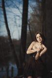 Brunetki dziewczyny stojaki drzewem blisko wody zdjęcie royalty free
