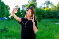 Brunetki Europejska dziewczyna w lecie w świeżym powietrzu Trzyma telefonów rejestry wideo Ono uśmiecha się pokazywać ręka gest obrazy royalty free