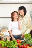 Brunetki gospodyni domowa z mężczyzna kucharstwem z świeżymi warzywami przy hom Zdjęcia Royalty Free