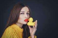 Brunetki kobieta całuje żółtej gumowej kaczki z czerwonymi wargami Zdjęcia Royalty Free