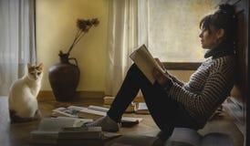 Brunetki kobieta czyta książkę na podłodze obraz royalty free