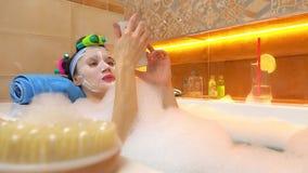 Brunetki kobieta jest ubranym twarzy maski klepnięcia na jej smartphone w foamy wannie Zdjęcie Stock