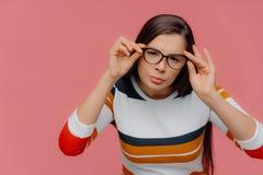 Brunetki kobieta koncentrująca w odległość, spojrzenia thorugh okulistyczni szkła skrupulatnie, utrzymuje ręki na obręczu, baczne obraz stock