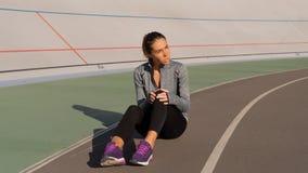 Brunetki kobieta krzywdzi jej nogę podczas ranku bieg na śladzie obraz royalty free