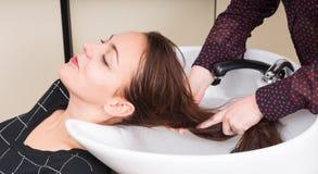 Brunetki kobieta Ma włosy Myjącego w salonie obraz stock