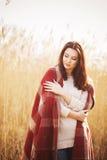 Brunetki kobieta outdoors w czeka wzoru szkockiej kraty ono uśmiecha się Zdjęcia Royalty Free
