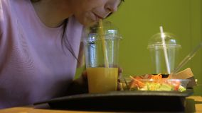Brunetki kobieta pije świeżego sok pomarańczowego od plastikowego szkła przez słomy zdjęcie wideo