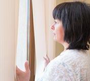Brunetki kobieta przyglądająca out okno Obraz Stock