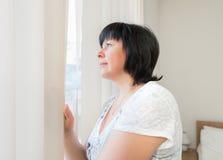 Brunetki kobieta przyglądająca out okno Fotografia Stock